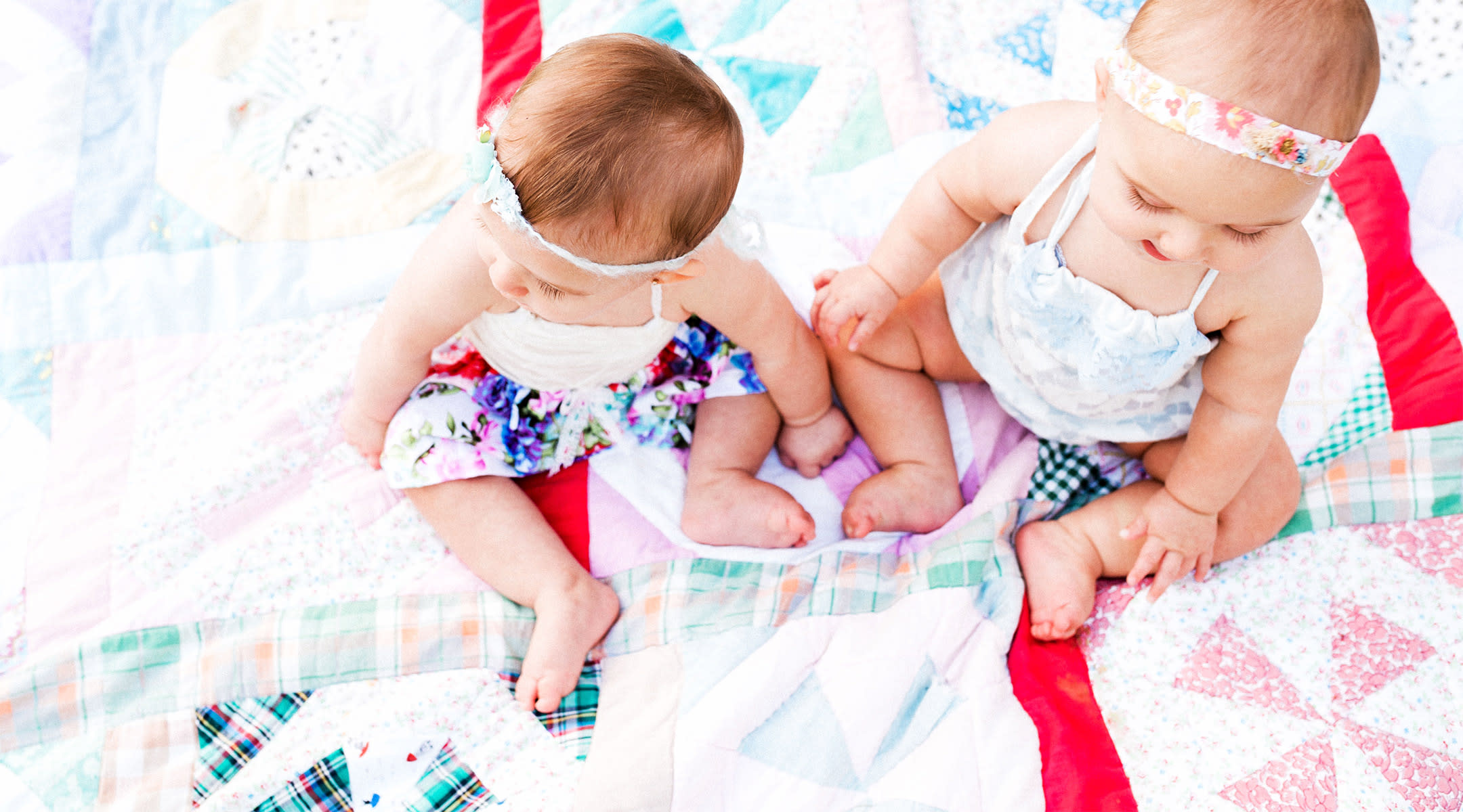 twins playing outside on blanket
