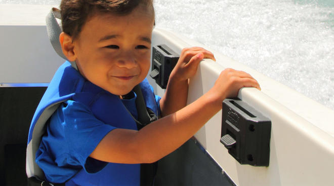 toddler boating on the open water and wearing a life vest