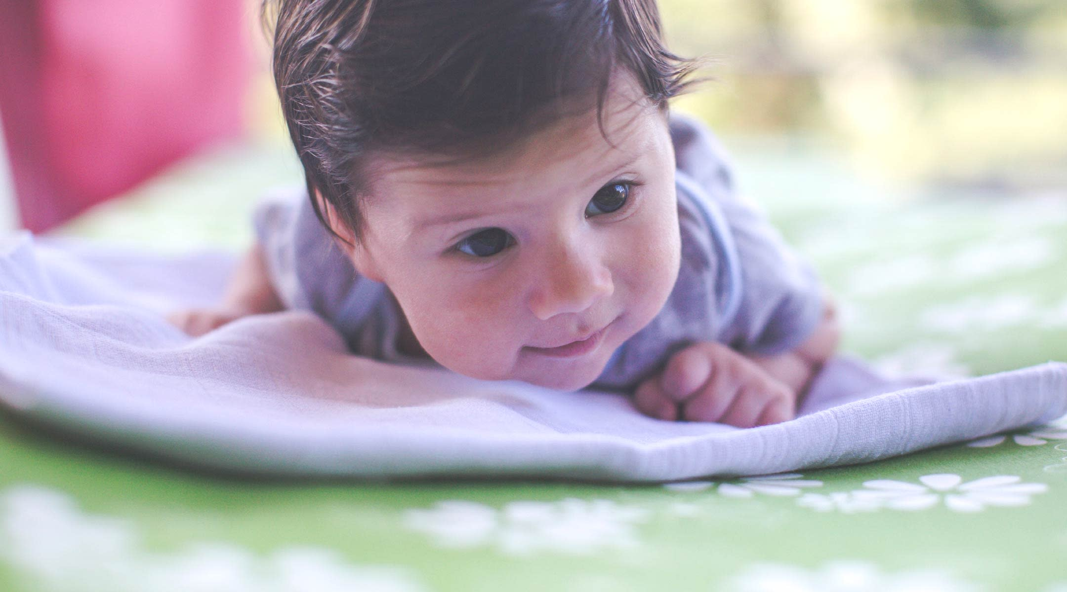 Baby with little smile doing tummy time.