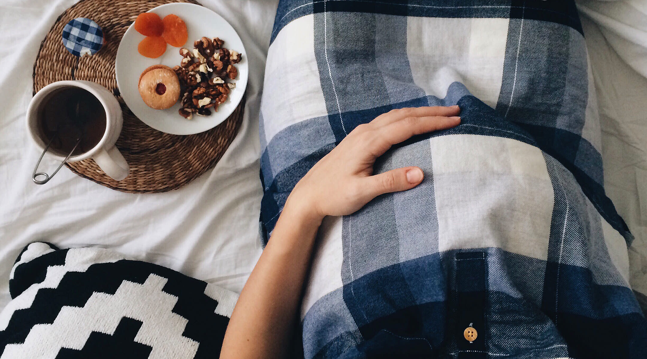 pregnant woman in bed with plate of food