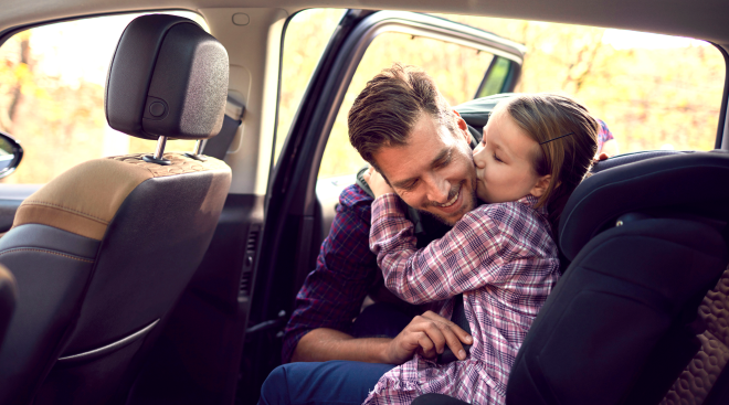dad buckles in young daughter as she kisses him