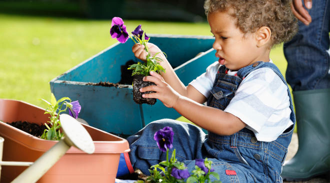toddler planting flowers in a garden