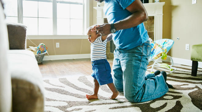 baby with dad learning to walk