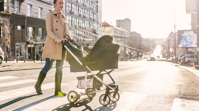 mom pushing stroller in a city setting