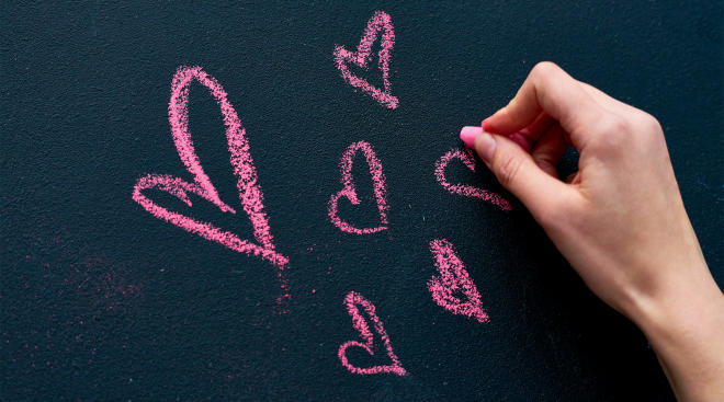 person drawing hearts on chalkboard with pink chaulk