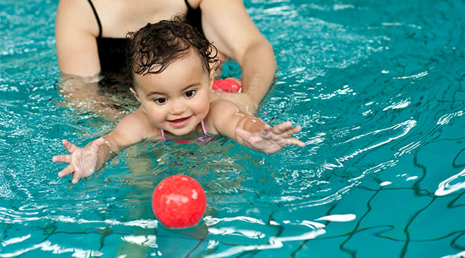 baby being held by its mother swims towards ball in pool