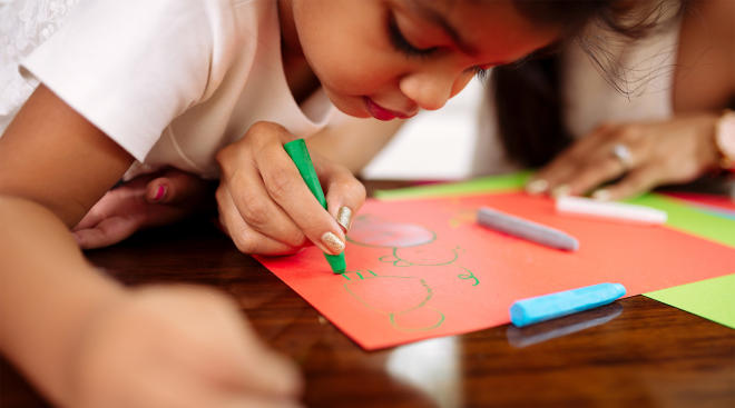 preschool age child draws during craft time