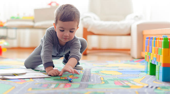 Little boy playing by himself on a play rug that shows roadways and cars.