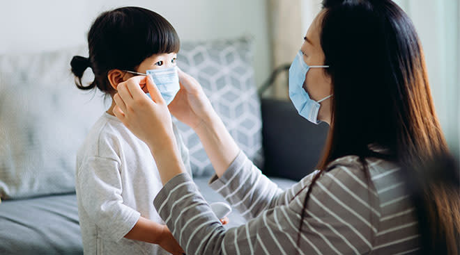 Mom helping her daughter put on a mask.