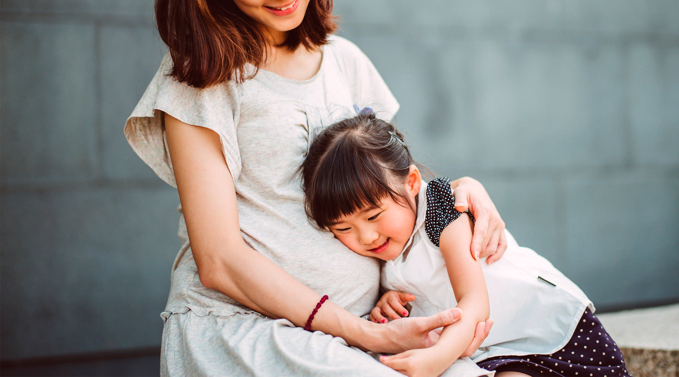 daughter hugging pregnant mom