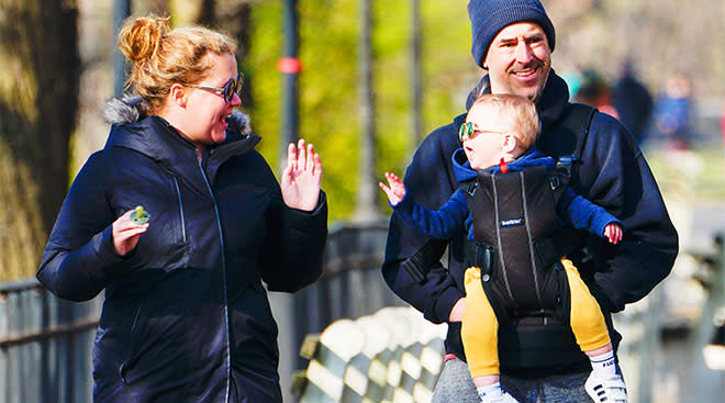 amy schumer with her bay son and husband walking in the park