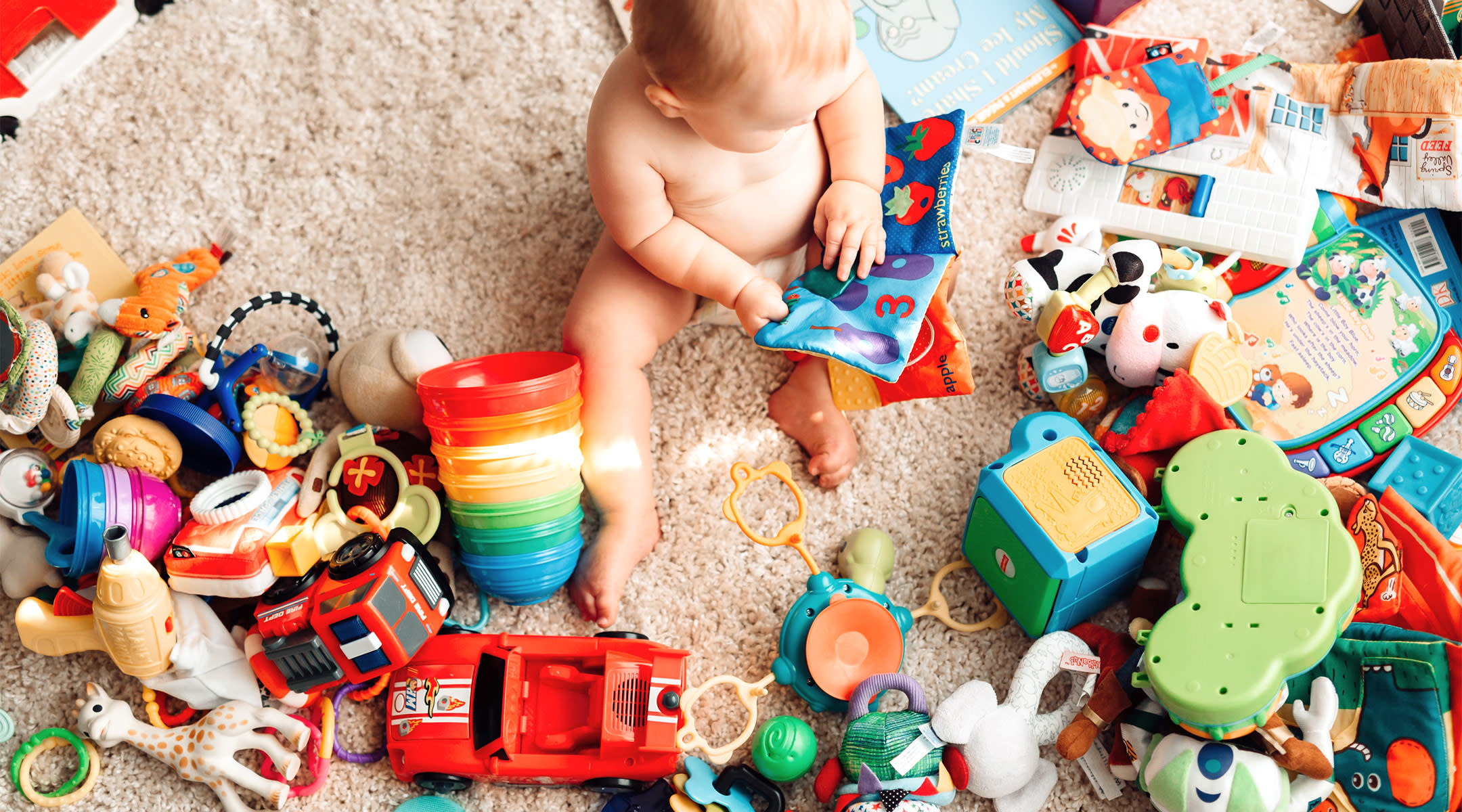 baby sitting on the floor with a bunch of toys