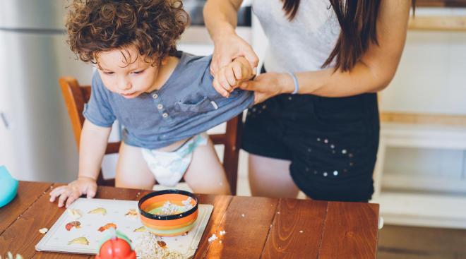 mom holding her toddler's arm after he spilled hi breakfast
