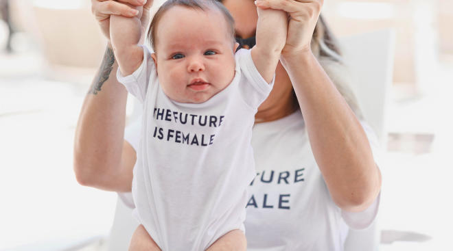 writer mom holding her baby daughter with onesie that says the future is female