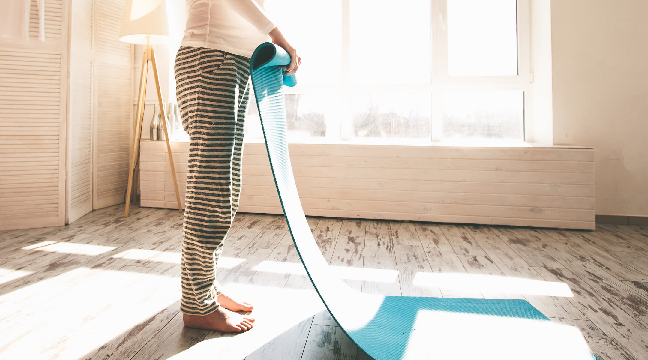 pregnant woman rolling up yoga mat after exercising at home