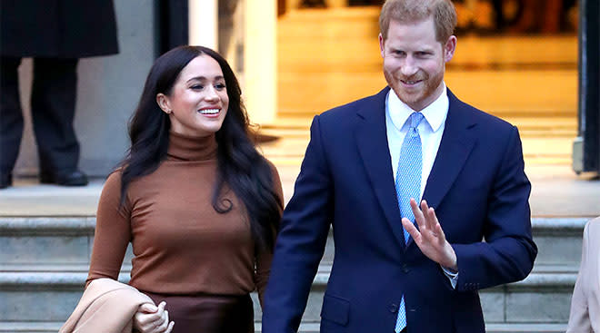 Meghan Markle and Prince Harry walking down stairway, smiling and waving.