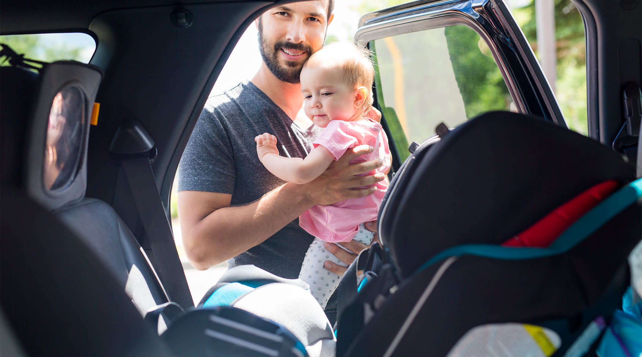 car seat safety, dad putting baby into her car seat