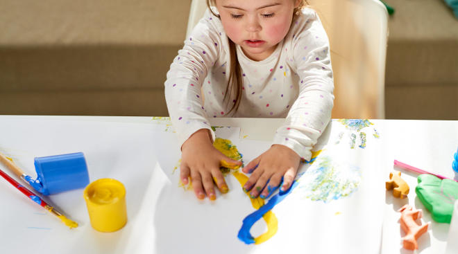 toddler using paint to make art at table