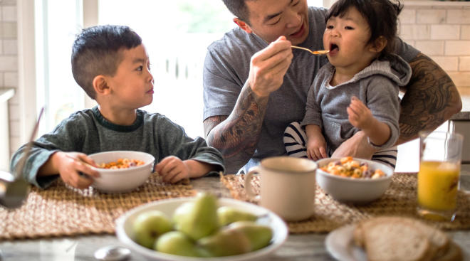dad with his two young children eating breakfast