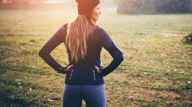 proud smiling woman stands outside in work out clothes