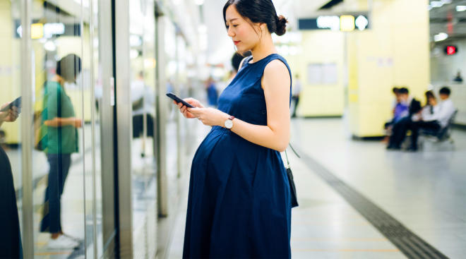 pregnant woman waiting to get on the metro