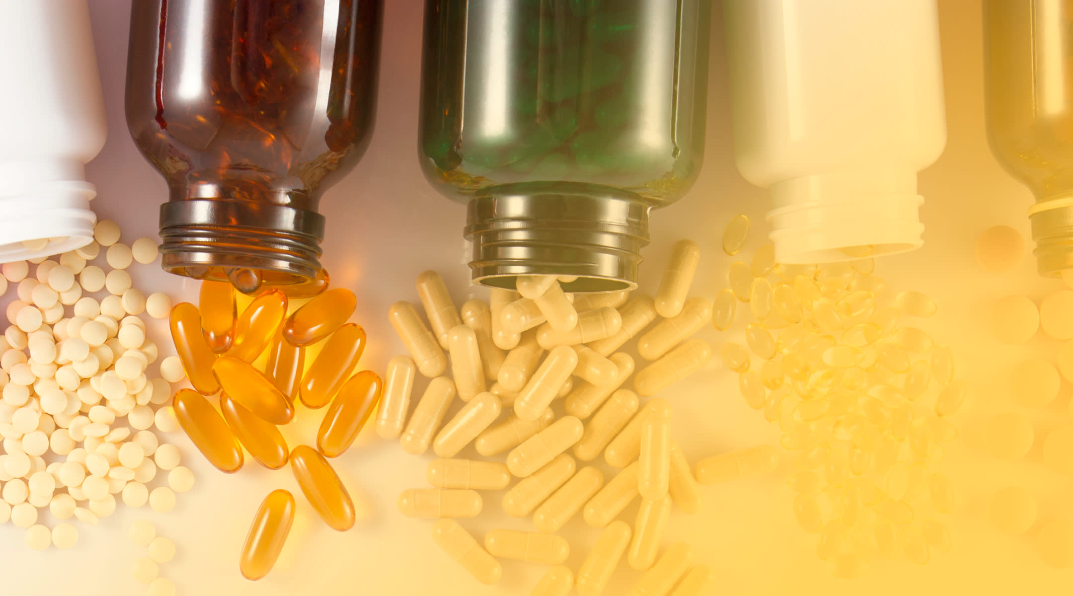 vitamin bottles with vitamins spilling out