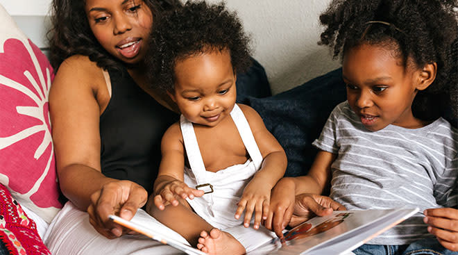 mom reading to her two young daughters in bed
