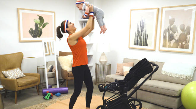 happy mom holding and exercising with her baby