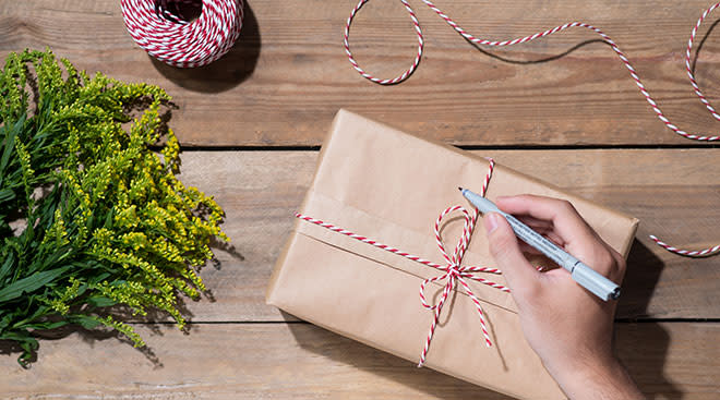 brown paper wrapped package next to yellow flowers