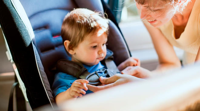 baby boy being strapped into car seat by mom