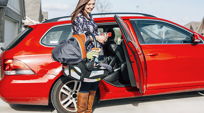 mom holding car seat about to put baby in her red car