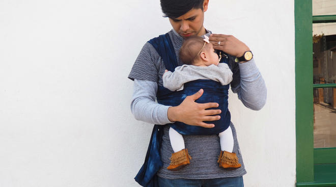 dad walking outside and holding baby correctly in carrier to avoid hip dysplasia