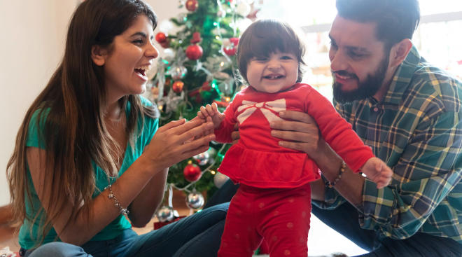 parents holding up baby in her red christmas outfit