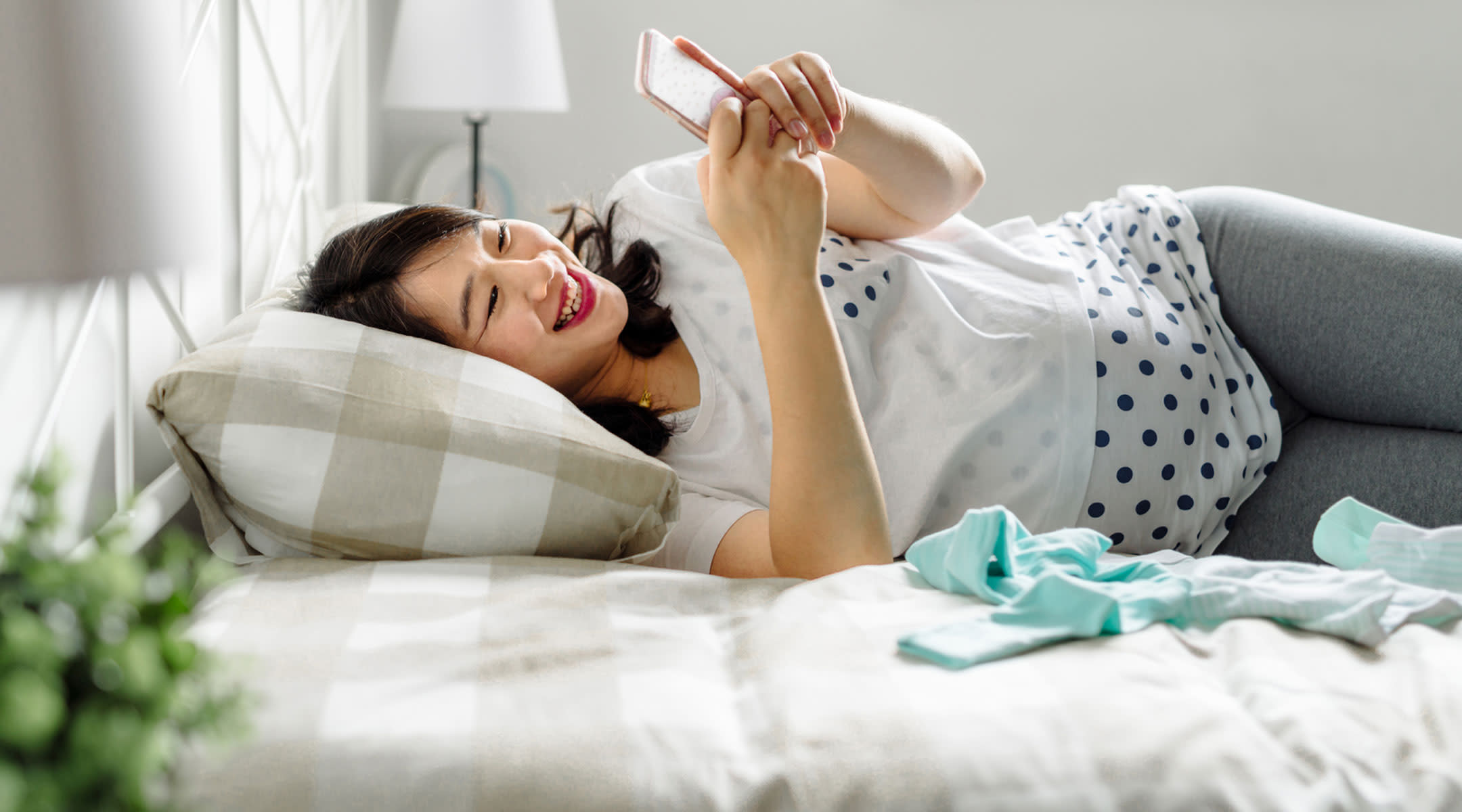 Pregnant woman laying on her bed and looking at her phone.
