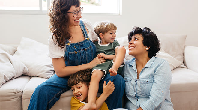 Same sex parents cuddle with their two young children at home.