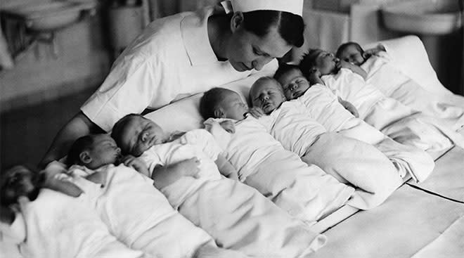Vintage black and white photo showing newborns in a hospital with a nurse close-by.
