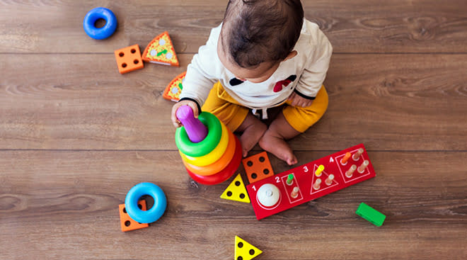 baby sitting on floor and playing with toys