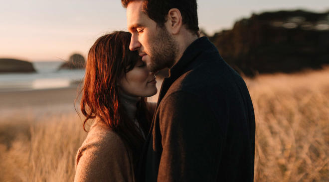 contemplative couple embraces in beautiful outdoor scenery