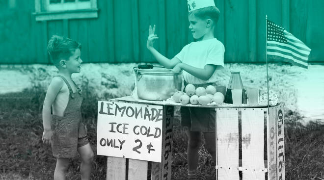little boy buying lemonade from a stand