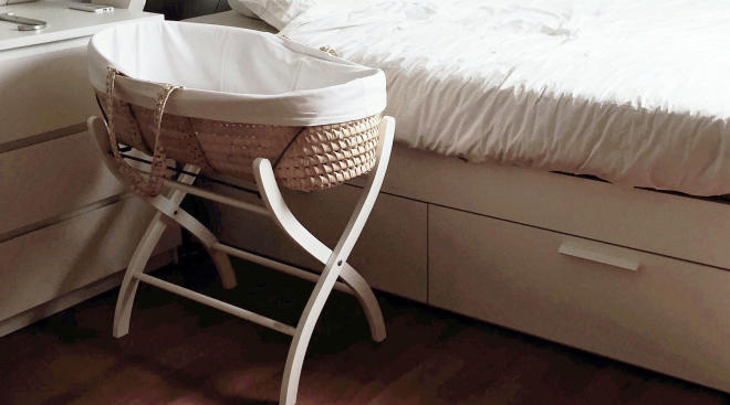 Baby bassinet in parents' bedroom.