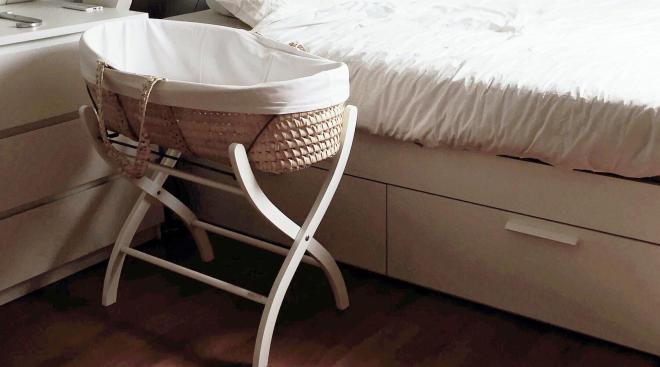 Baby bassinet in parents' bedroom.