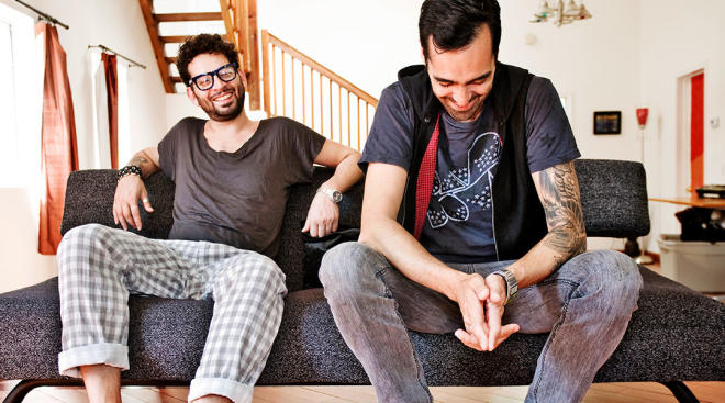 two men sitting on couch at home laughing
