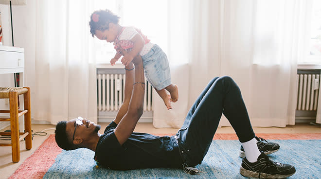 dad holding his toddler while laying on the floor at home