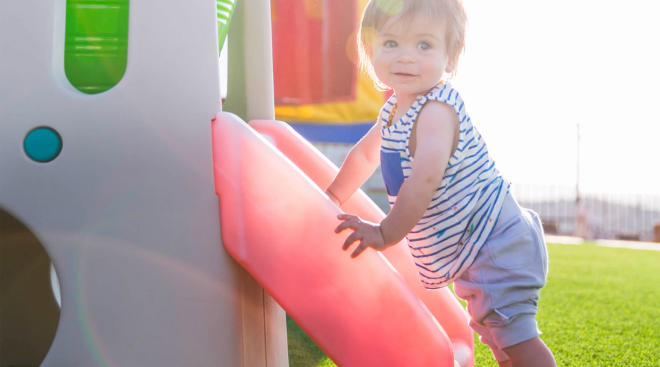 toddler playing outside on playground