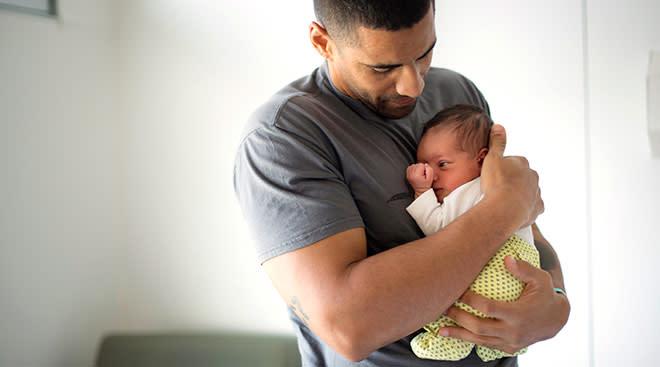 new dad holding his newborn baby close