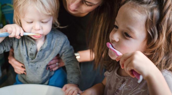 toddler siblings brushing teeth together