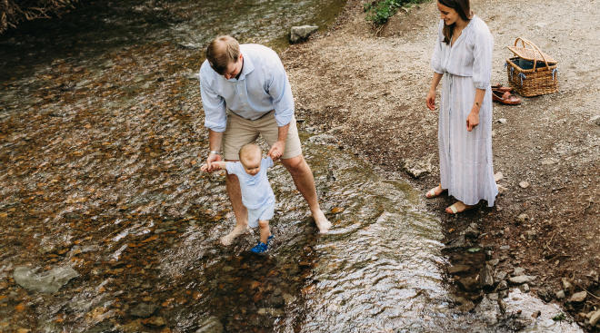 parents take baby on a walk by the creek for a summer time activity