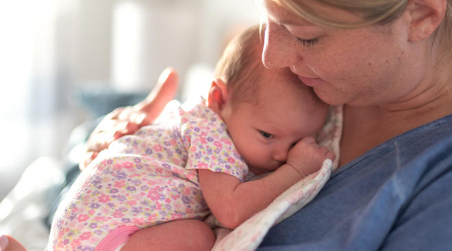 new mom holding her newborn baby after delivery