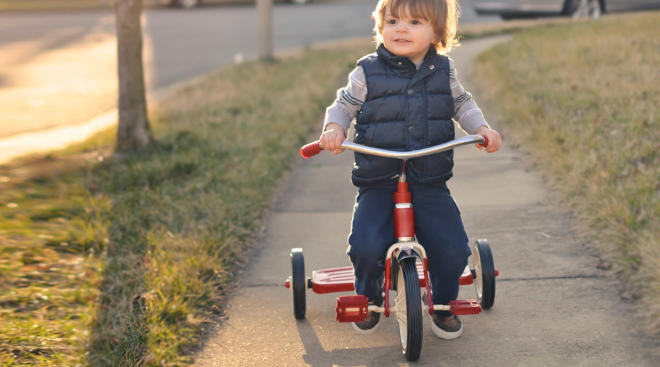 toddler riding his tricycle through neighborhood