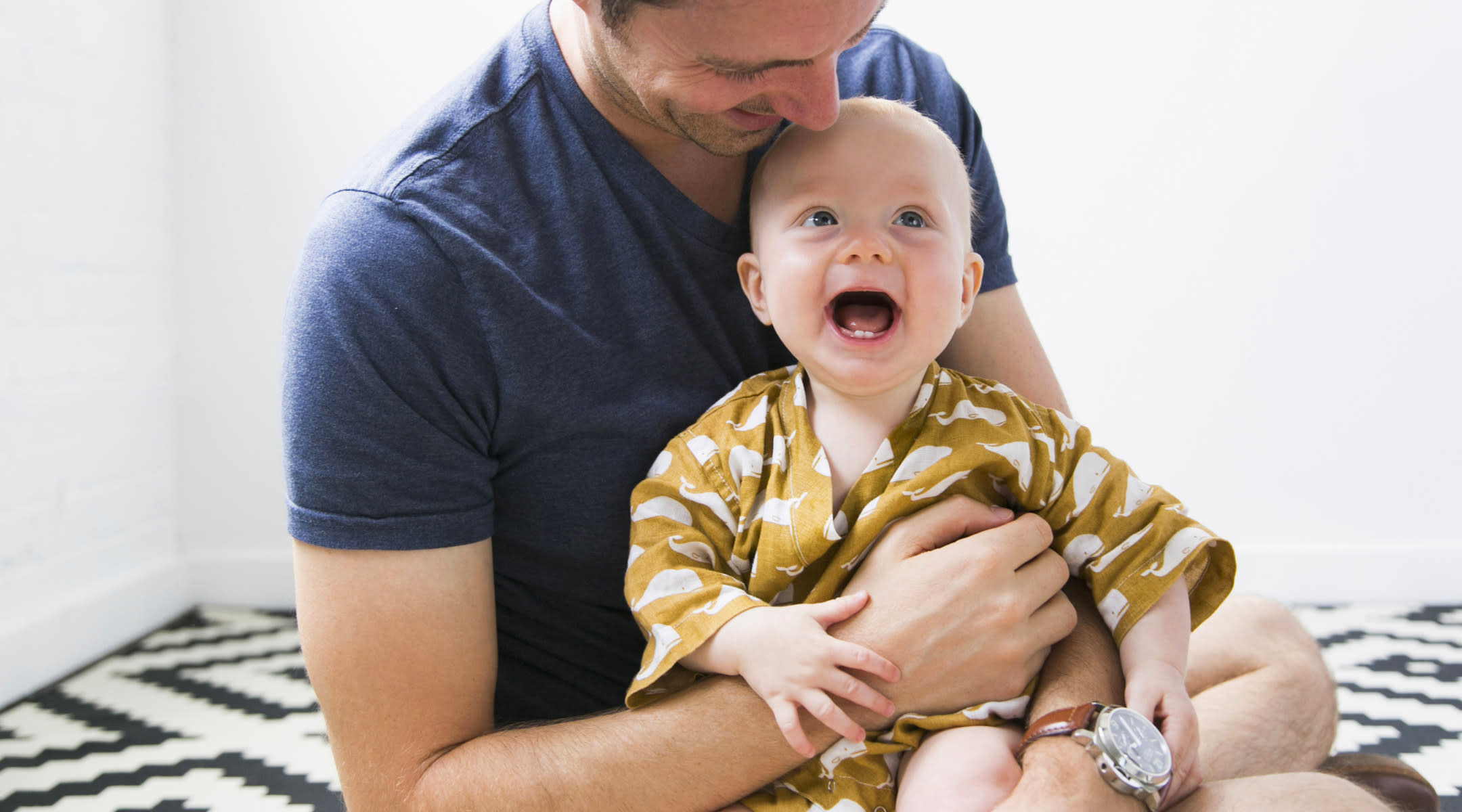 Dad holding excited baby.